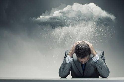 Mand sidder med hænderne på hovedet og en regnsky over sig