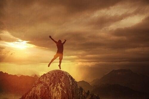 En mand hopper af glæde på toppen af et bjerg