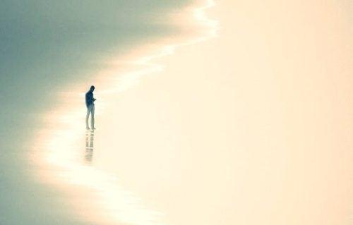 Mand går alene på strand og oplever postmoderne ensomhed