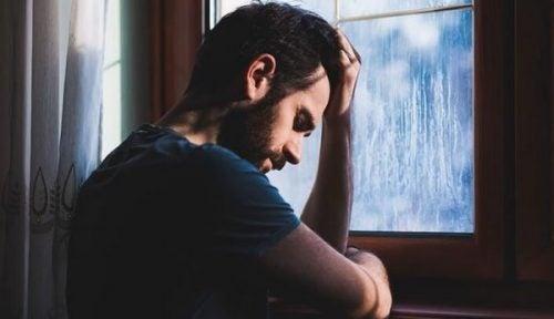 Mand tager sig til hovedet og er frustreret over ikke at kunne overvinde apati