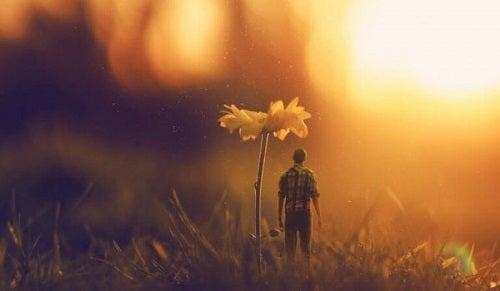 En lille mandefigur står under en blomst