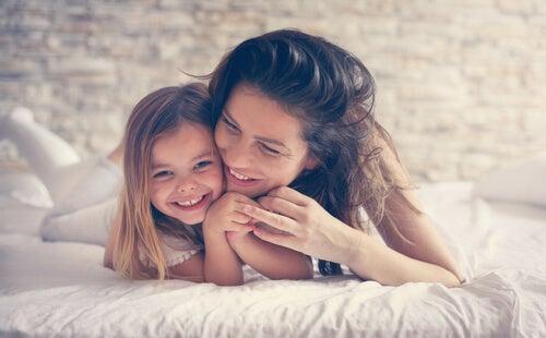 En mor krammer sin datter i seng