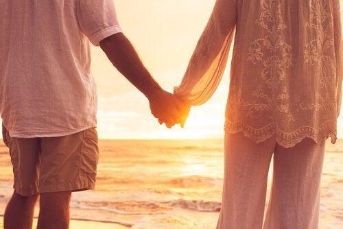 Et par der holder i hånd på en strand