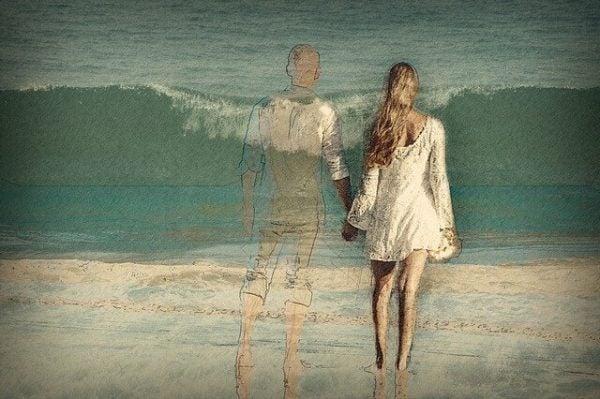Kvinde står med silhuet af mand foran hav