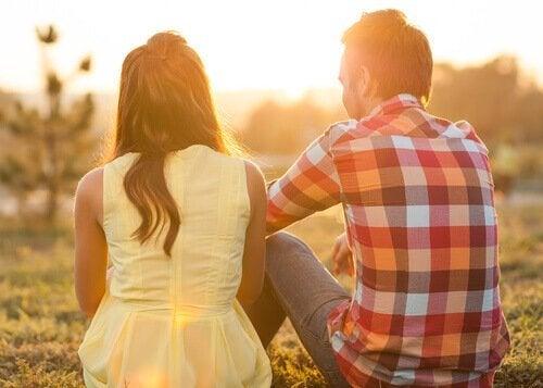 To personer sidder og snakker på græsplæne
