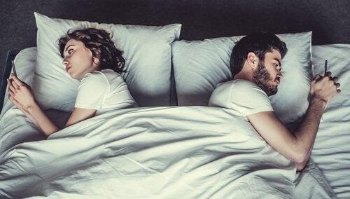 Par i seng kigger på telefoner og lider under seksuel anoreksi