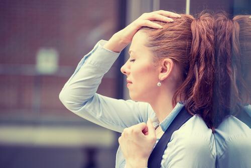 Stresset kvinde læner sig op af en mur