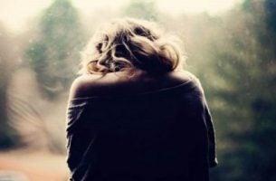 Trist kvinde står med bøjet hoved på grund af reaktiv depression