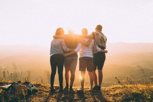 Venner står og krammer foran solopgang
