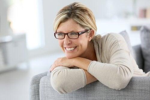Kvinde sidder med briller sidder i sofa