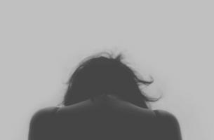 Kvinde med bøjet hoved lider under ar fra misbrug