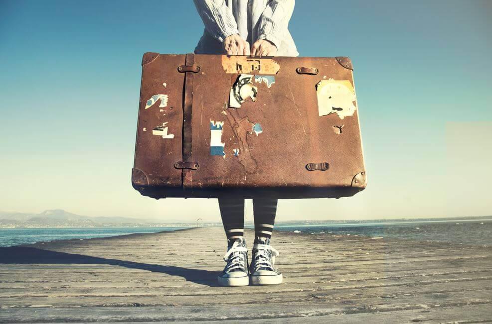 Person står med stor baggage, der symboliserer personlighed, som kan analyseres med 16PF personlighedstest