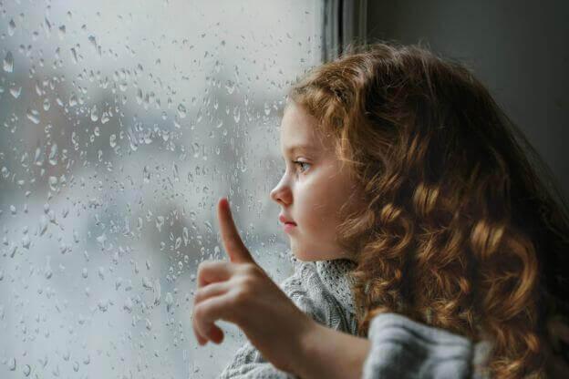Lille pige ser på regn på vindue