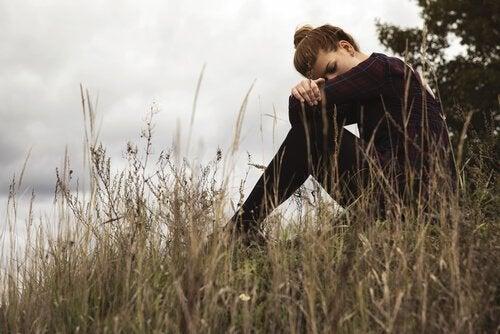 Kvinde på mark hviler hoved på knæ