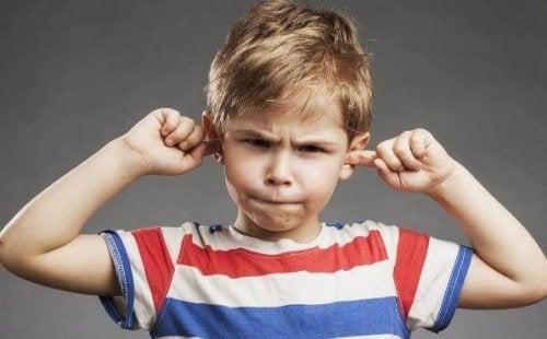 Dreng kommer fingre i ørerne