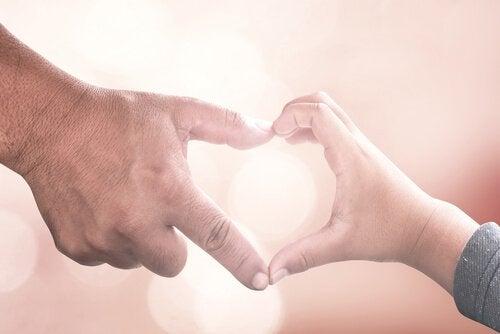 Lille hånd og stor hånd danner hjerte