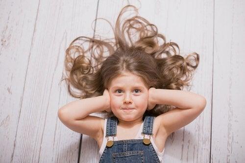 Lille pige på gulv har hænderne for ørerne