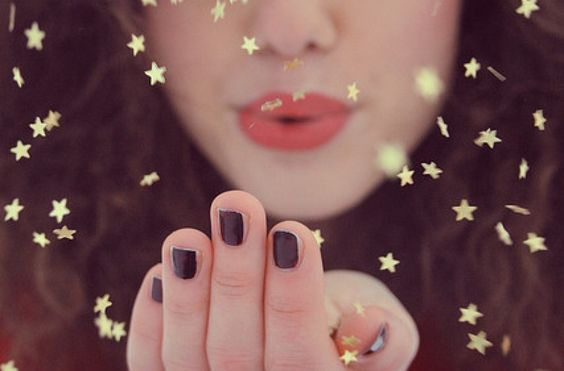 Kvinde puster små guldstjerner