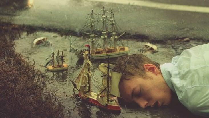 Mand sover i miniatureland med skibe