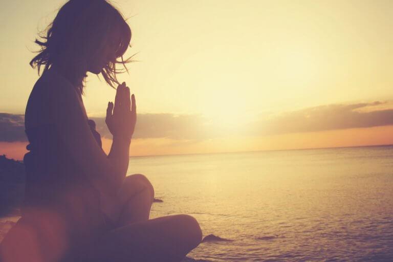 Kvinde mediterer ved hav