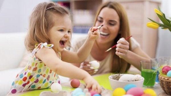 Pige maler påskeæg med sin mor