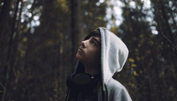 Ung teenager i skov med hættetrøje på