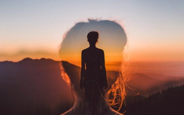 Kvindes silhuet foran bjerglandskab