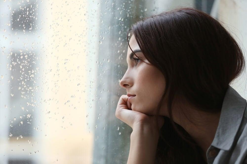 Trist kvinde, der ser ud af vindue med regn på, har behov for bøger til at overvinde depression