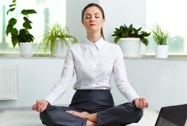 Kvinde mediterer i rum med planter