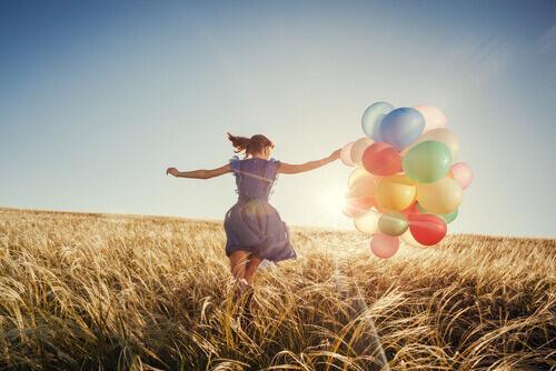 Glad kvinde løber på mark med balloner