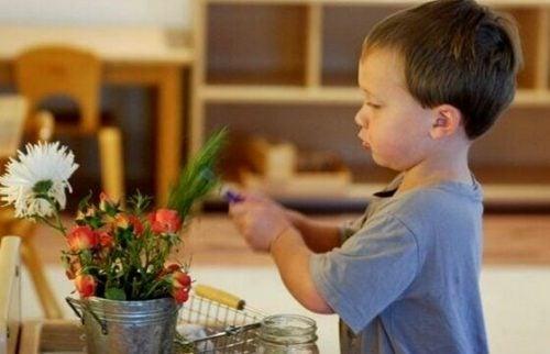 Barn, der leger med en plante