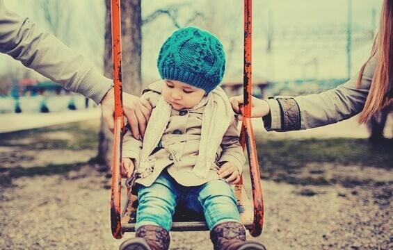 barn på gynge med deleforældre