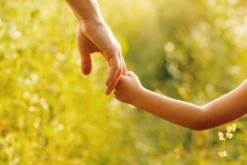 Et barn og en voksen, der holder i hånd