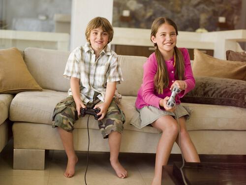 Børn sidder på sofa og spiller videospil