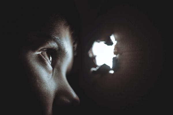 Lille dreng kigger ud af vindue i papkasse