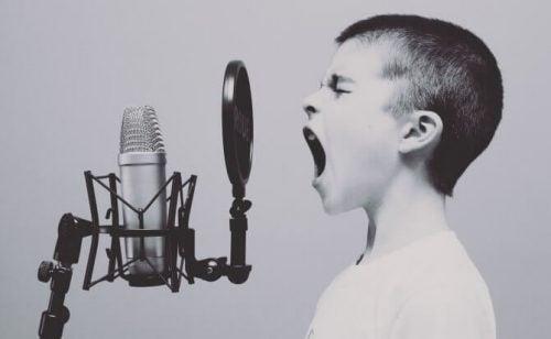 Dreng, der råber ind i en mikrofon