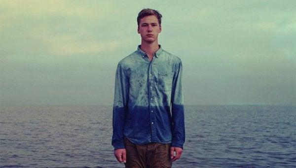 Mand foran hav går i et med horisonten