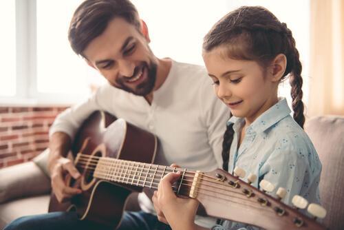 Pigen hjælper med at spille på guitar