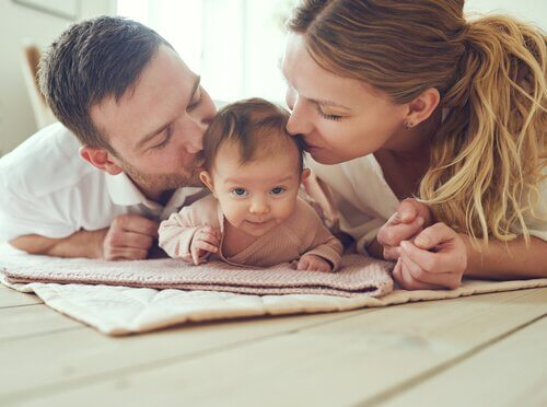 Forældre kysser datter på hoved