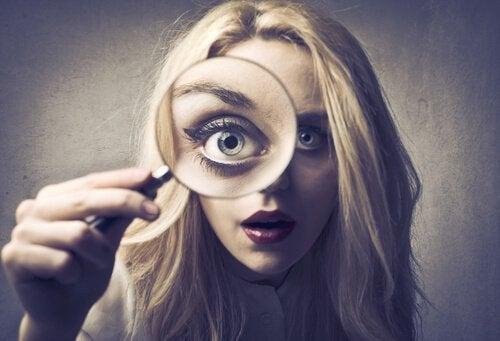 Kvinde, der er for selvkritisk, kigger i forstørrelsesglas
