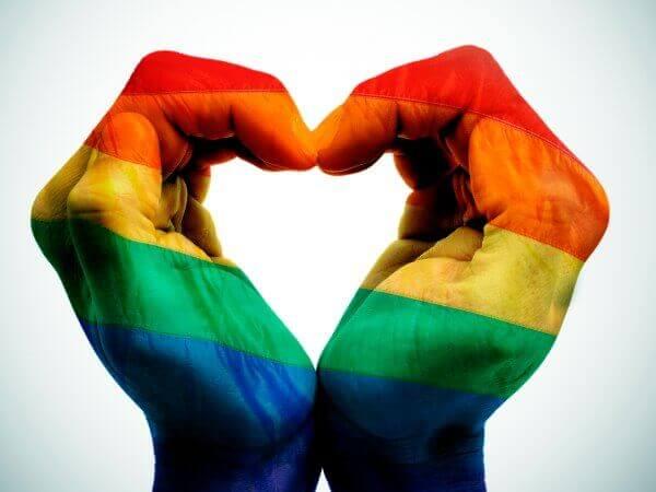 Hænder danner hjerte med regnbueflag