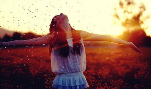 en pige med hænderne ud til siden i landskab