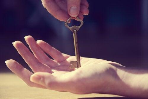 Hånd, der låser sig selv op med en nøgle