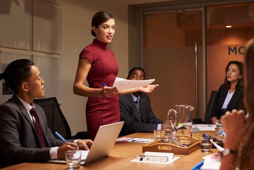 Kvinde holder tale til møde