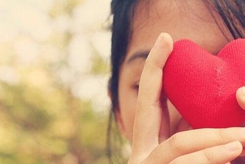En kvinde der holder et hjerte foran sit ansigt