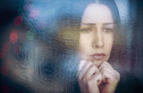 Kvinde, der kigger trist ud af vinduet, lider af dystymi