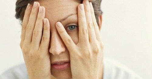 Kvinde der kigger ud gennem fingrene