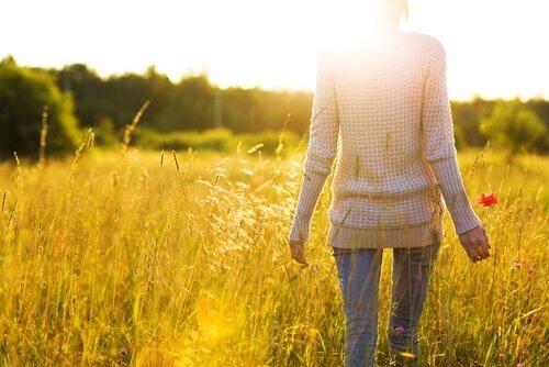 Kvinde går på mark mod sollys