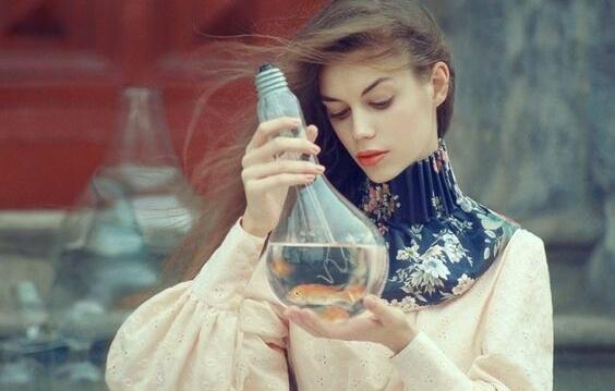 kvinde med en kolbe med væske og guldfisk