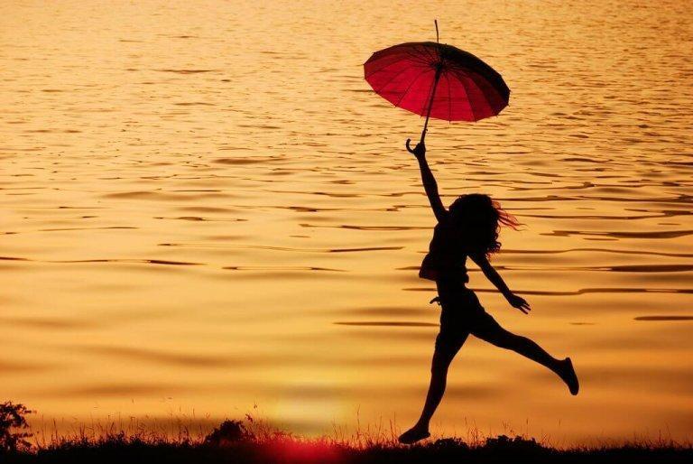 Glad kvinde i solnedgang ved sø